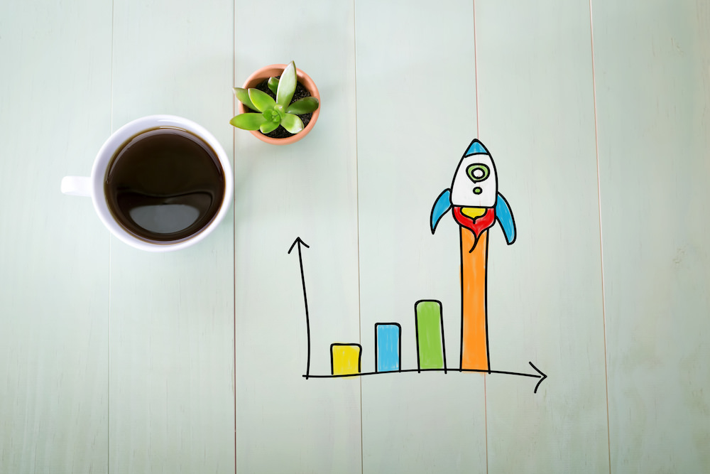Person drawing Rocket graph concept on white paper in the office